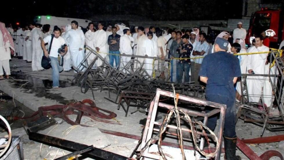 BORTE PÅ TRE MINUTTER:  Sjokkerte mannlige bryllupsgjester, som var samlet i et separat lokale etter kuwaitisk skikk, kommer til branntomta der 41 kvinner og barn døde og 58 ble skadd da partyteltet brant ned lørdag kveld. Foto: NASSER WAJEH, AP/SCANPIX.