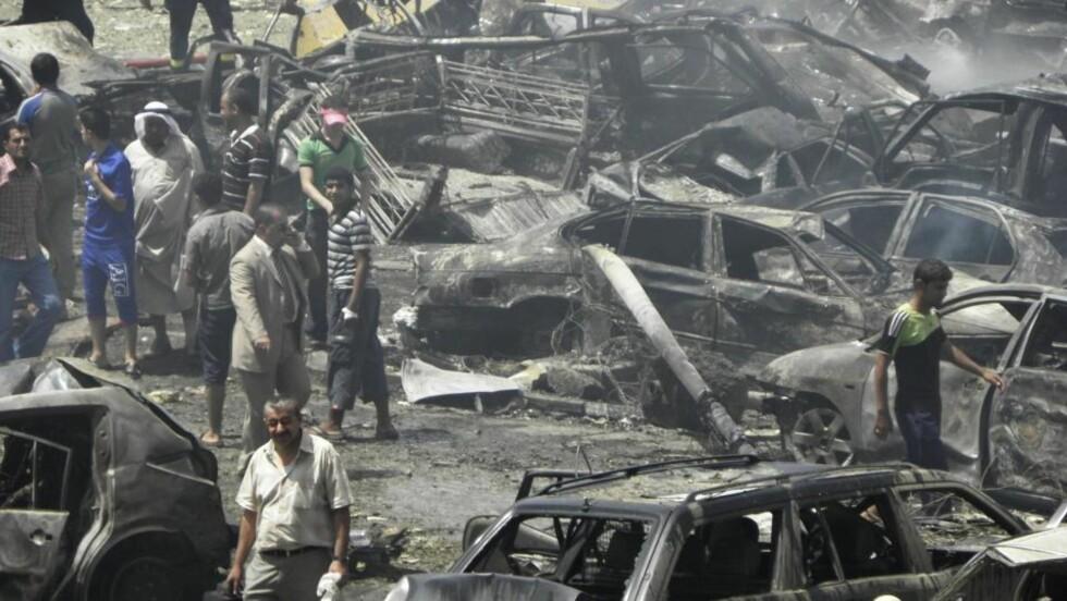 BILBOMBE: Innbyggere samles for å se på ødeleggelsene etter de mange angrepene i Bagdad i morges. Foto: REUTERS/Ahmed Malik/SCANPIX