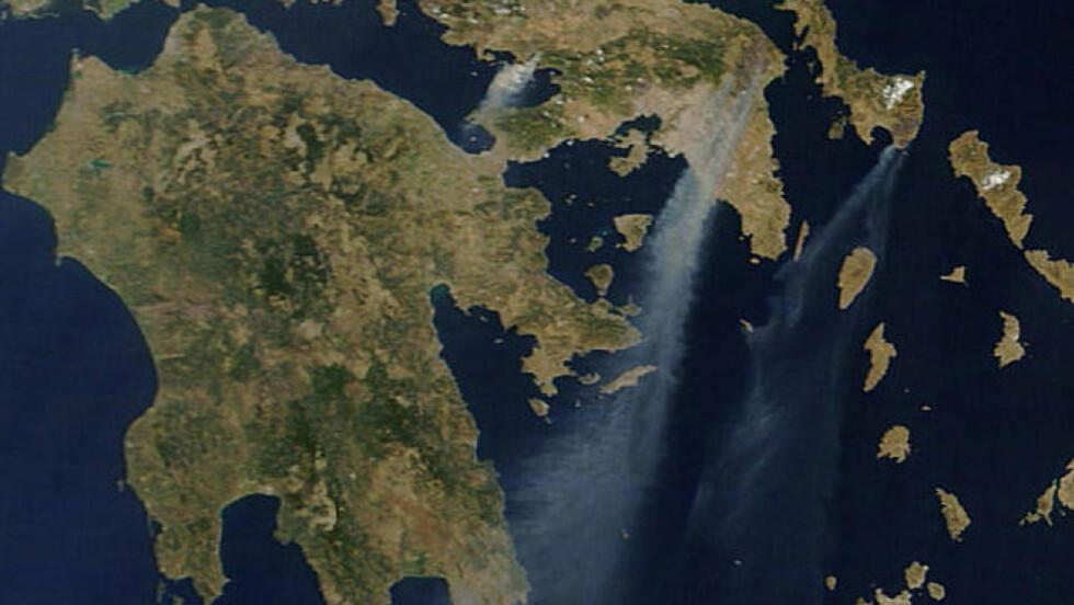 """FRA SATELITT:  Brannsituasjonen rundt Aten sett fra ESA-satellitt i morges.""""Den kraftige røykstripa i midten kommer fra Aten-området og Marathon-området. Røyken til høyre fra ferieøya Evia og røyken til venstre fra området sør for Thiva. Foto: AFP/ESA/SCANPIX."""