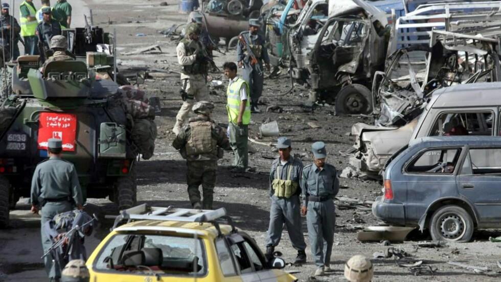 BLODIG ÅR: Afghanske sikkerhetsstyrker og ISAF-soldater fra NATO sikrer etter åsted etter at en selvmordsbomber kjørte forsøkte å kjøre inn i en kortesje fra NATO. To ble drept og flere skadd i angrepet tidligere denne måneden. Foto: EPA/SCANPIX