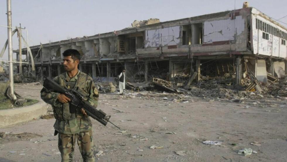 MINST 43 DREPT: En afghansk soldat står utenfor åstedet for bombeangrepet i Kandahar i Sør-Afghanistan tirsdag. Taliban nekter for å stå bak angrepet. Foto: AP/SCANPIX