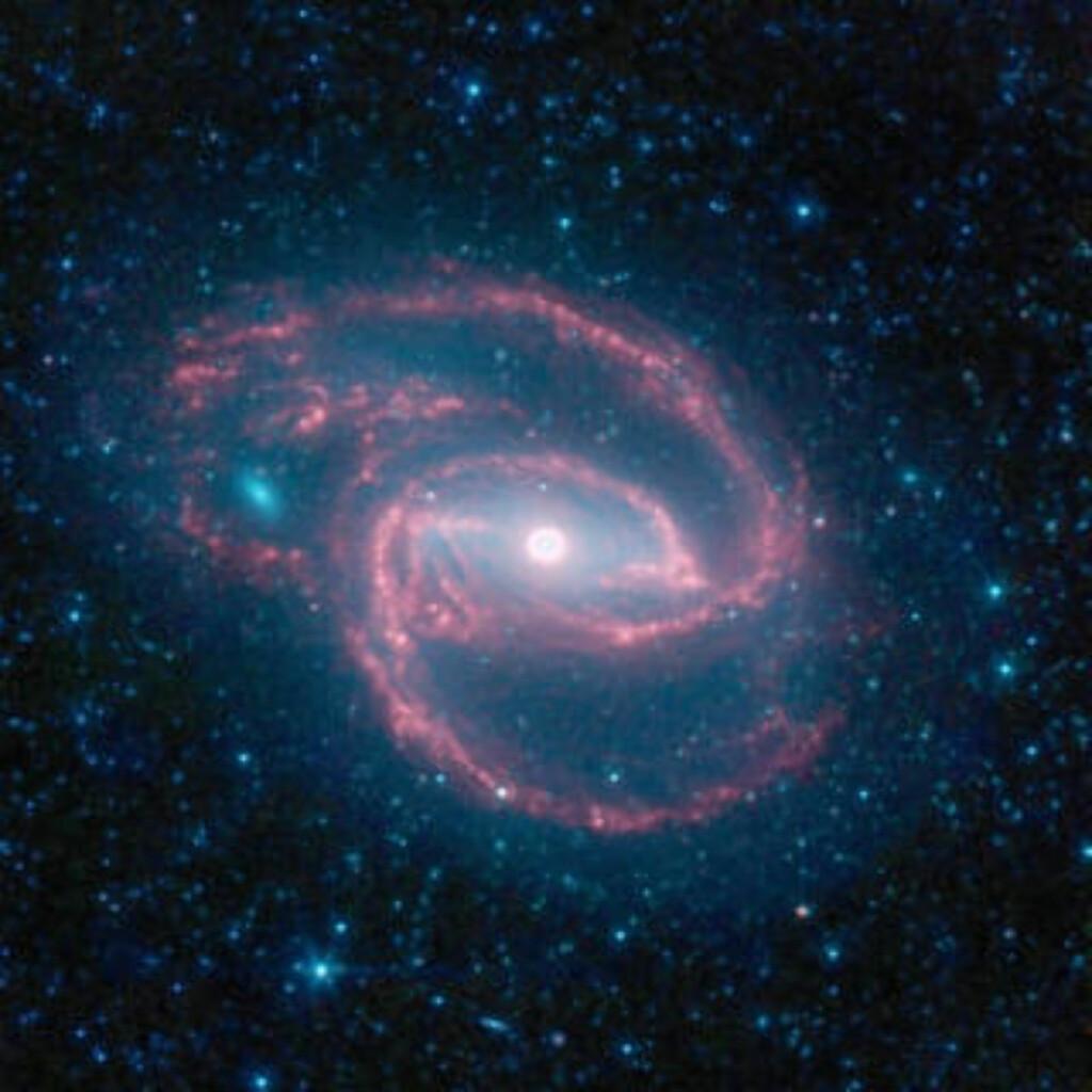 SNURRIG: NASAs Spitzer-teleskop tok nylig dette bildet av en spiralgalakse døpt NGC 1097. Midt inne i galaksen finner man et gigantisk svart hull - trolig 100 millioner ganger mer massivt enn vår egen sol. Disse supermassive svarte hullene finnes trolig i sentrum av alle galakser. Foto: AFP PHOTO/NASA/JPL-CALTECH/Scanpix
