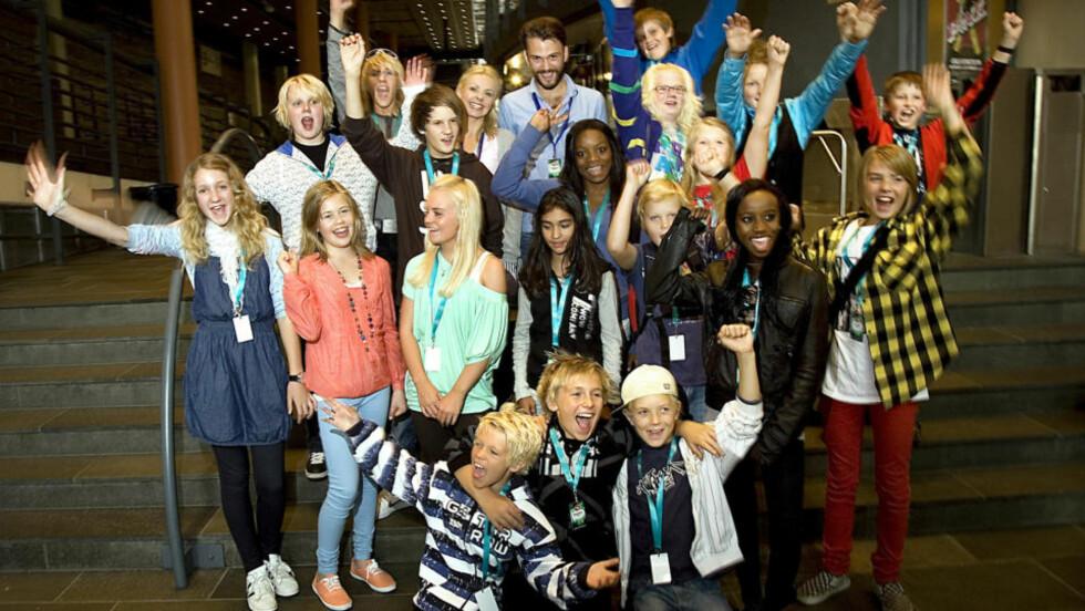 ET STJERNELAG: Her ser vi alle årets norske MGP junior-deltakere. Lørdag kveld kan vi følge dem på NRK1 direkte fra Oslo Spektrum. I midten et stykke bak står programlederne Marthe Sveberg Bjørstad og Kåre Magnus Bergh.       Foto: Anders Grønneberg