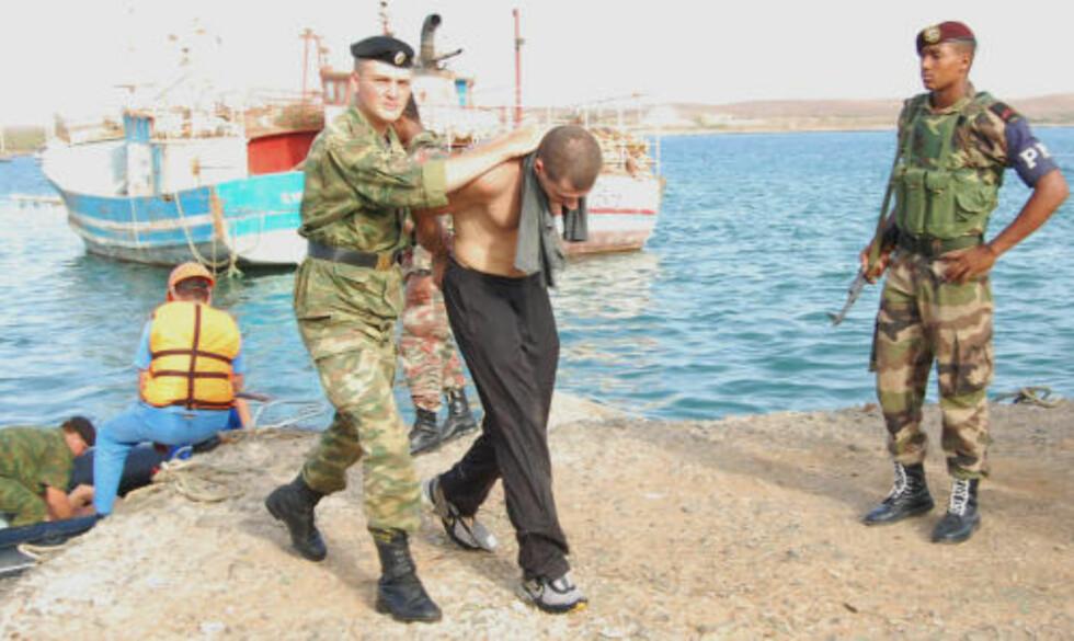 KAPRER: En av kaprerne blir ført i varetekt av en russisk soldat. Foto: AFP PHOTO / Scanpix
