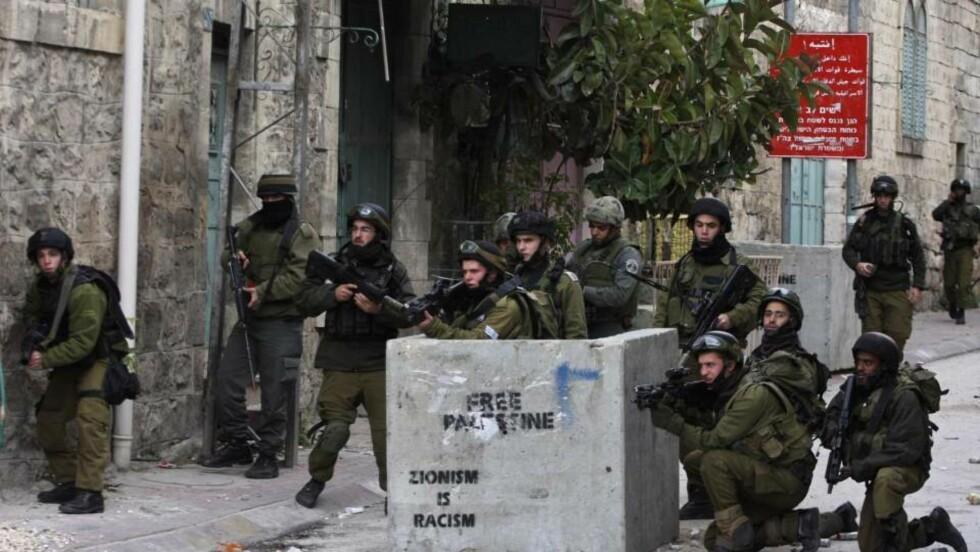 TROPPER GJØRES KLARE: Her går israelske soldater i stilling under sammenstøt med palestinske demonstranter i Hebron i dag. Foto: AP