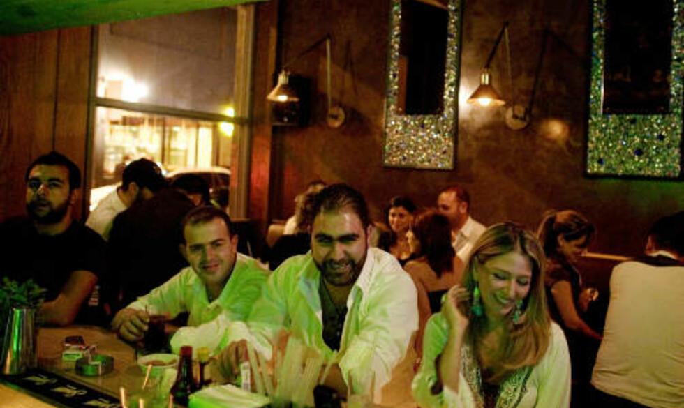 SPANDABEL BAREIER: 28-årige Patrick Ghosn (midten) har drevet baren Rehab i Gamayzeh i litt over ett år. Jeg anbefaler dere å reise til Beirut. Finnes ikke mer gjestfrie mennesker på jord, sier Ghosn, før han nipper til sin n'te whisky for kvelden.Foto: Torbjørn Grønning