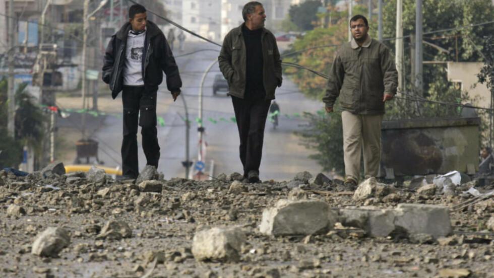 FORTSETTER ANGREP: Tirsdag kveld fortsetter angrepene mot Gazastripen. Her går tre menn i gatene i Gaza by tirsdag. Foto: AP/SCANPIX