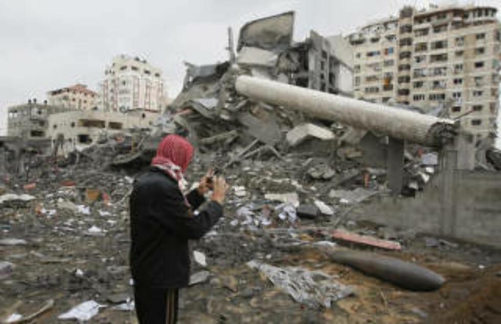 <strong>STORE ØDELEGGELSER:</strong> En palestinsk mann tar et bilde av en israelsk bombe som ikke gikk av, like ved justisdepartementet som ble truffet tidligere i dag. FOTO: AFP PHOTO/MAHMUD HAMS/SCANPIX