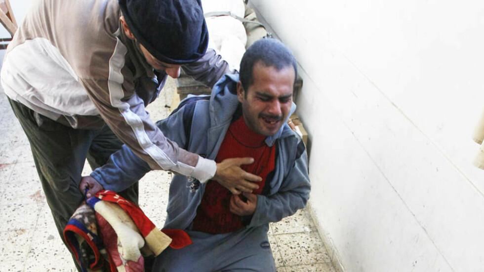 GRÅTER OVER SINE DØDE BARN: Magdi al-Samuli  sørger over sine tre døde barn på likhuset i Shifa-sykehuset i dag. Seinere ble en familie på sju utradert. Foto: MAHMUD HAMS / AFP / SCANPIX