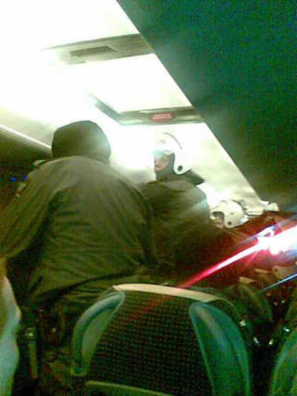FRAKTET TIL POLITIHUSET: Her står politiet inne på bussen og passer på de innbrakte. MMS-foto: Privat