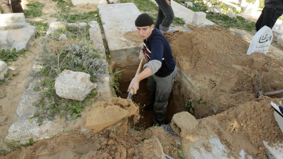 GRAVLEGGER FETTEREN: En palestinsk mann graver en grav til fetteren sin på Sheikh Redwan-gravstedet i Gaza by. Gravstedet har følgende skilt ved inngangen: Gravstedet er fullt. Foto: REUTERS/Mohammed Salem/SCANPIX