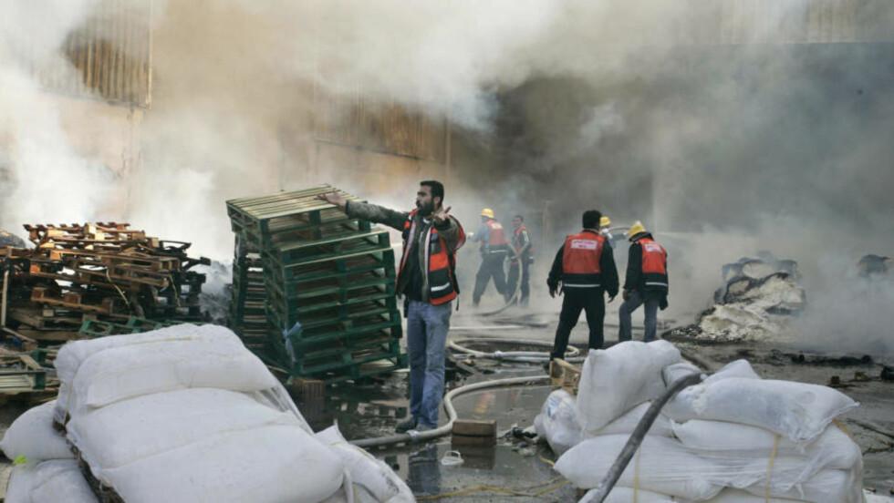 I BRANN: FN-arbeidere og palestinske brannfolk arbeider med å slukke brannen i UNRWA-hovedkvarteret, og redde sekker med mat som ble oppbevart i en lagerbygning. Foto: HATEM MOUSSA/AP/SCANPIX