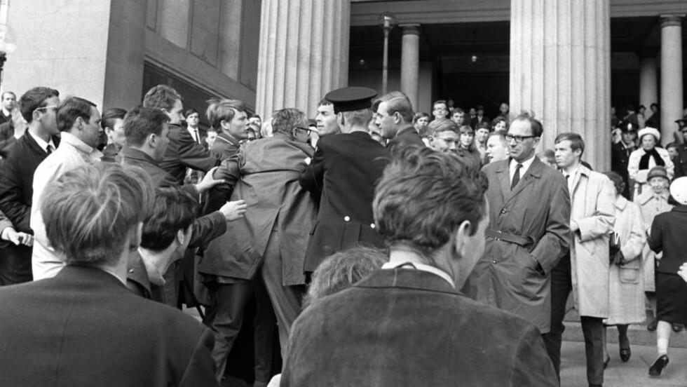 """""""LANGHÅREDE"""": Det syntes i alle fall VG disse Anti-Israel-demonstrantene utenfor Universitetets aula i 1968 var. Det var den første propalestinske demonstrasjonen i Norge, og møtt med fordømmelse på venstresida. Bildet viser politiet som til aksjon når gjestene som deltok på feiringen av Israels 20-årsdag kommer ut.  Foto:  Laurvik / NTB / Scanpix"""