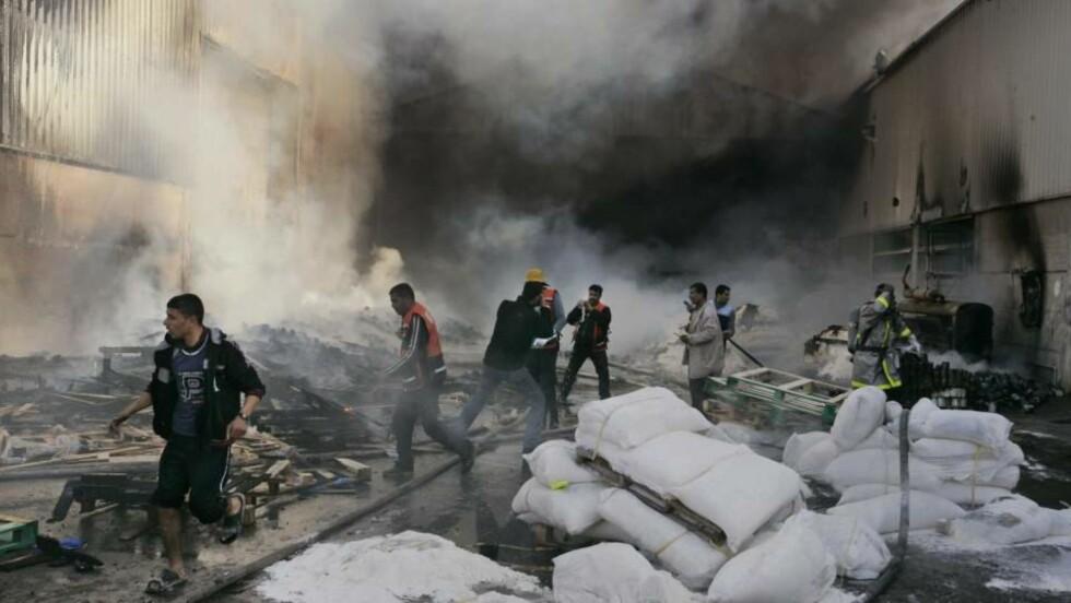 REDDER RESTENE: Brannfolk og FNs personell forsøker å redde restene etter at dette matlageret tok fyr i dag. Foto: AP/Hatem Moussa/SCANPIX