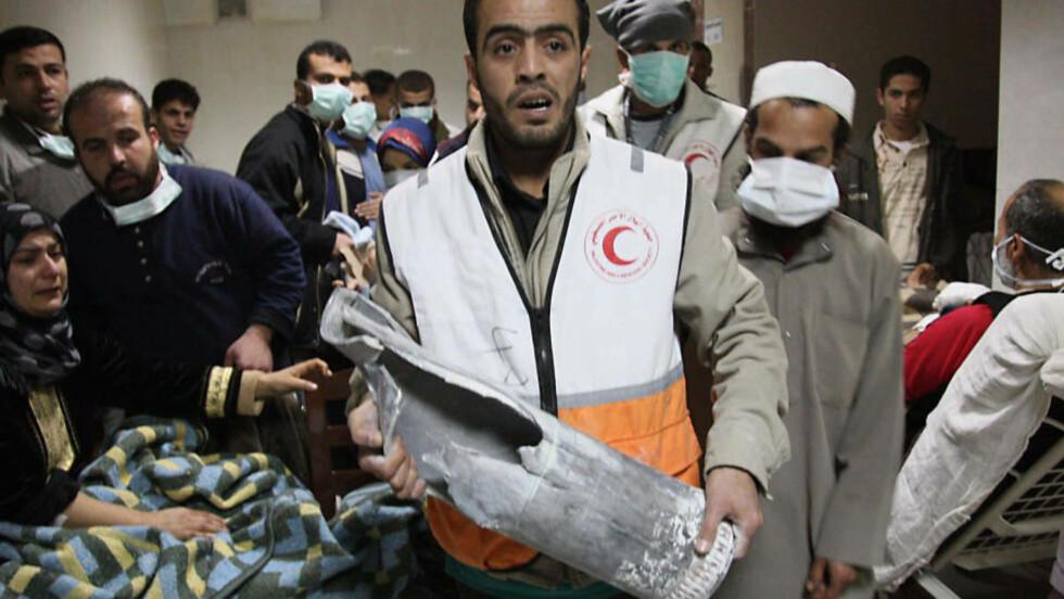 BOMBET SYKEHUS: En ansatt ved sykehuset Al-Quds til Røde Halvmåne i Gaza står igjen med restene av en bombe. Bak ham står pasienter med masker som skal beskytte mot alt støvet i bygningen. Flere hundre gjemmer seg på sykehuset i frykt for flere israelske bomber. Foto:AFP/MEHDI FEDOUACH/SCANPIX