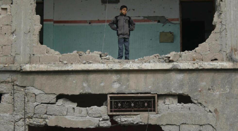 STORE ØDELEGGELSER: En palestinsk gutt titter ut av en sønderbombet bygning i Rafah, sør på Gazastripen i dag. Foto: AP Photo/Khaled Omar