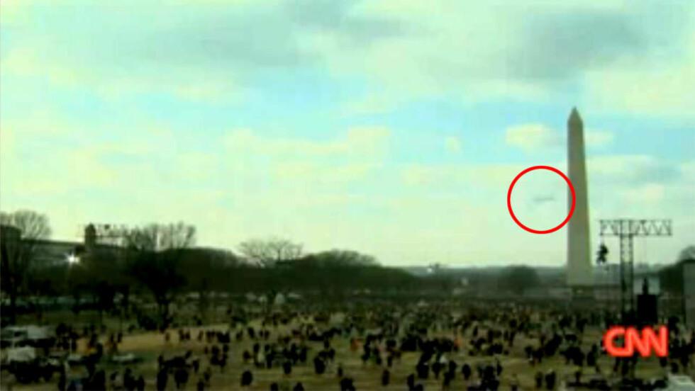 MYSTISK: Er det en UFO, eller er det bare en fugl. Det kan være en drone, eller kanskje supermann. Diskusjonen er heftig. Forøvrig er det ingen som biter seg merke i skikkelsen som henger i lysmasta... Faksimile: CNN