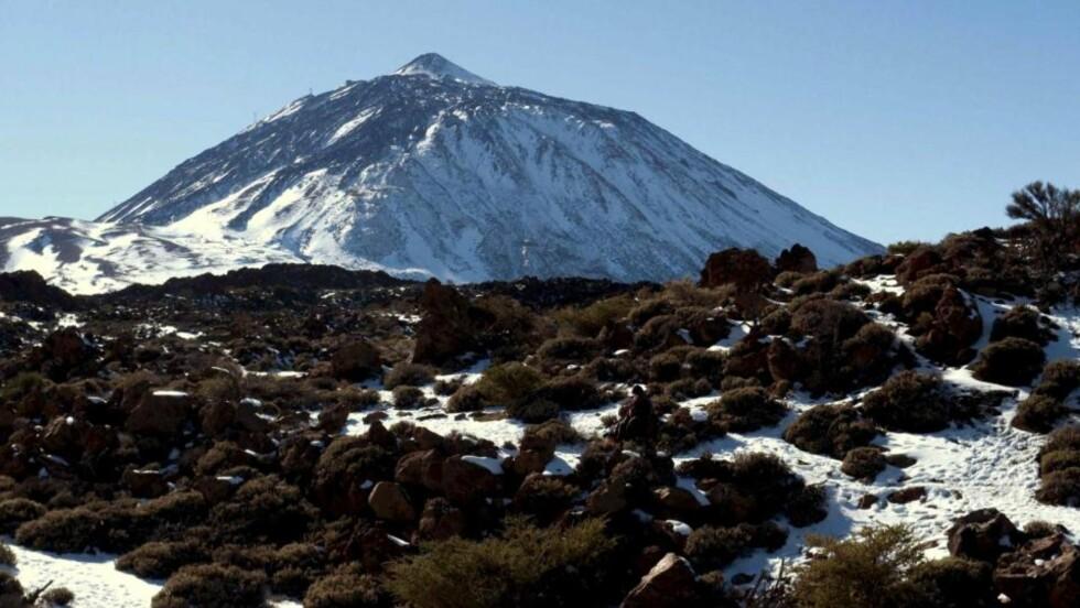SJELDENT SYN: Snø dekker vulkanen Teide og den omliggende nasjonalparken. Politiet har sperret veiene inn til de snødekte områdene for å hindre ulykker. Foto: Scanpix/EPA/Manuel Lérida