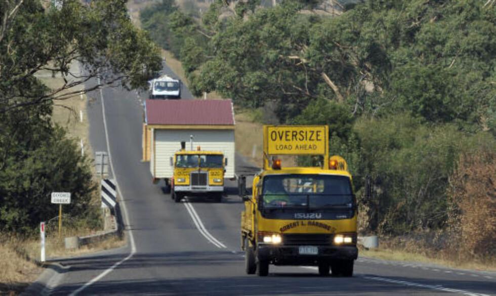 <strong>STENGER OG EVAKUERES:</strong> En tungtransport med en bygning finner veien ut av brannherjede Yarra Valley. I dag stenges hundrevis av skoler og barnehager i området på grunn av frykten for at brannene skal blusse opp igjen. Foto: AFP/Paul CROCK/SCANPIX