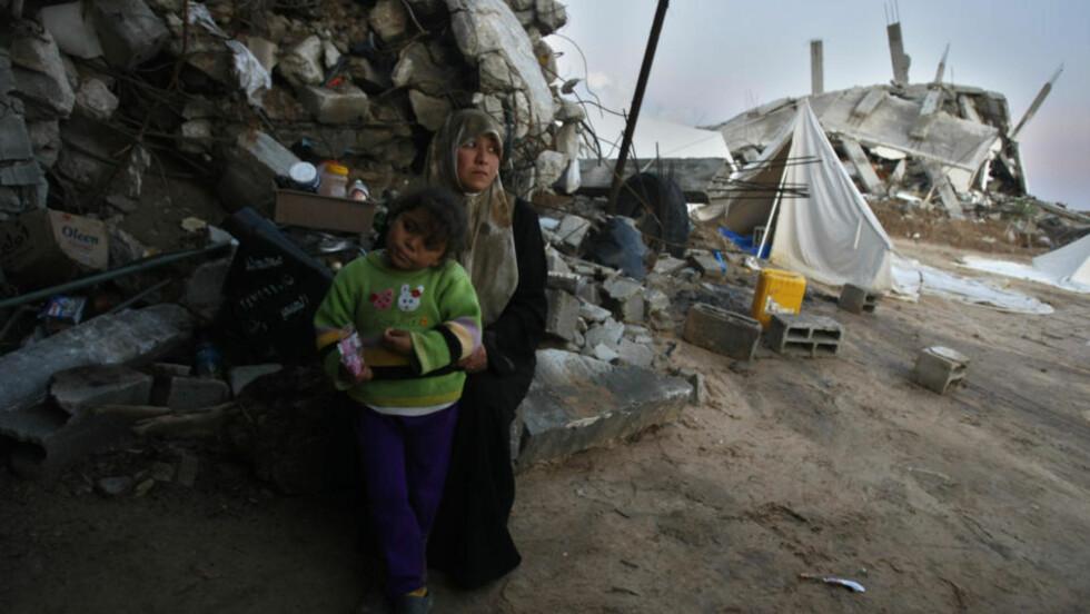 ENORME ØDELEGGELSER: En palestinsk kvinne og hennes datter sitter utenfor sitt raserte hus. Seks uker etter at kampene tok slutt ligger store deler av Gaza i ruiner. Foto: Mahmud Hams/Scanpix