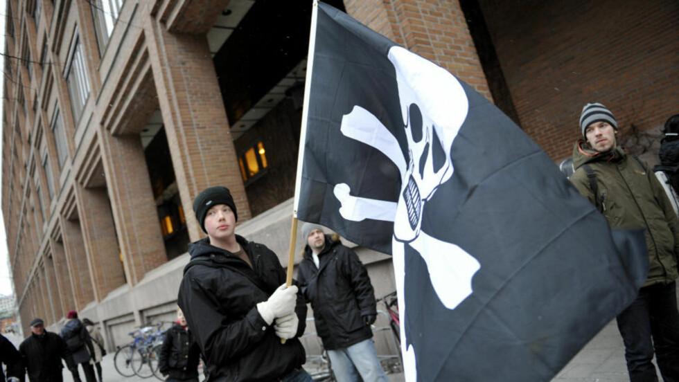FLAGGET TIL TOPPS, MEN IKKE I RETTSSALEN: Det var The Pirate Bays tilhengere som viste piratflagget under åpningen av rettssaken i Stockholm. Blant de tiltalte var bråkjekkhet og nettvisjoner erstattet av et systematisk forsøk på å bagatellisere The Pirate Bays betydning for nettsamfunnet, og de tiltaltes betydning for The Pirate Bay, skriver DB.nos kommentator. Foto: SCANPIX