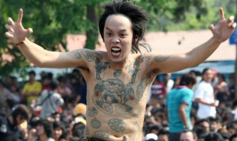 MIMER: Deltakerne mimer skapningne de har fått tatovert på kroppen: Foto: EPA/RUNGROJ YONGRIT/Scanpix