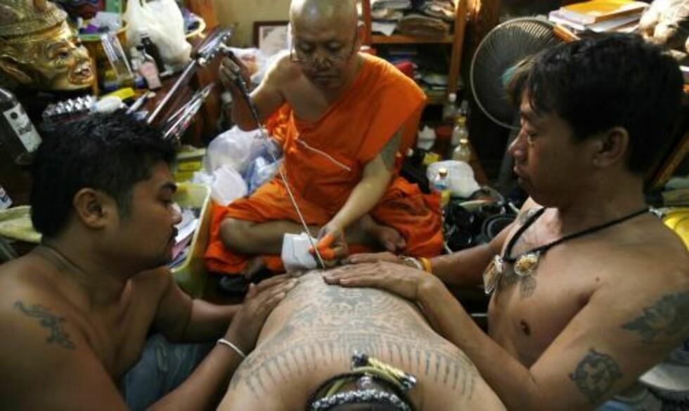 SKAL BESKYTTE MOT UFLAKS: Deltakerne blir tatovert av munker. Foto: REUTERS/Chaiwat Subprasom/Scanpix