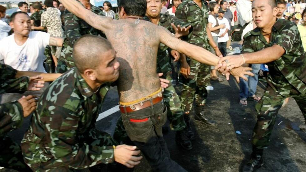 MISTET KONTROLLEN: Soldater måtte ta hånd om denne mannen under dagens festival. Foto: REUTERS/Chaiwat Subprasom/Scanpix