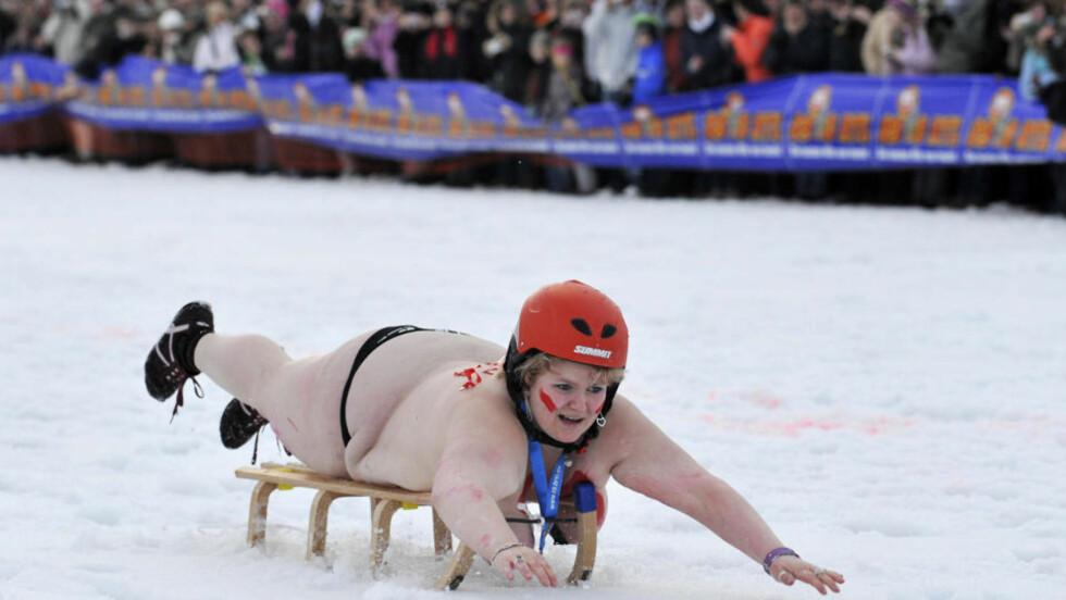 SLEDEKJØRING: En kvinne prøver å stikke av med seieren i det nakne sledeløpet som ble avholdt i Braunlage, Tyskland. AFP PHOTO DDP /  STEFAN SIMONSEN GERMANY OUT