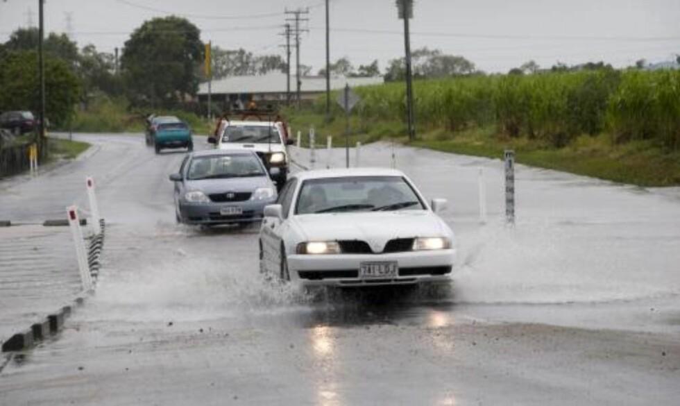 """FLYKTER: Turister og innbyggere i byen Mackay, nord for Brisbane, kjører gjennom flomvannet forårsaket av syklonen """"Hamish"""". Foto: SCANPIX/EPA"""
