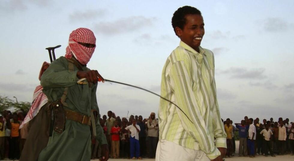 SHARIASTRAFF: En islamistkriger fra al-Shabab bruker pisken mot en ung mann som har tilstått voldtekt. Bildet er tatt i Mogadishu denne uka. Mannen var en av fire. De ble stilt på rekke i offentlighet. Folkemengden fulgte med mens de fikk straffen. Al-Shabab har fått innført sharialover i landet. Foto: REUTERS/Feisal Omar