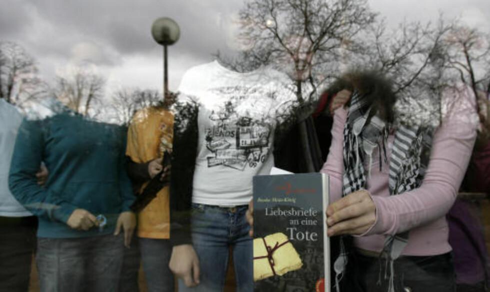 MEDELEVER: En elev ved skolen holder fram en skole med tittelen som kan oversettes som «Kjærlighetsbrev til en død». Foto: Latz/Ddp/Scanpix