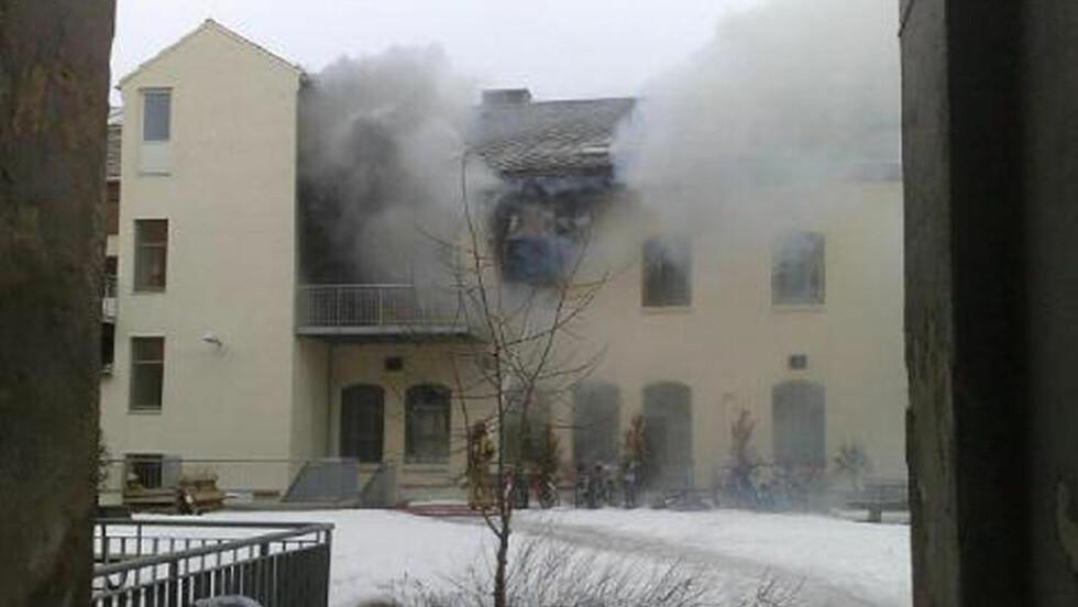 SPREDTE SEG MOT TAKET: Det brenner i en boligblokk i Trondheim, og en person er hentet ut med stige. MMS-foto: Roger Bremnes