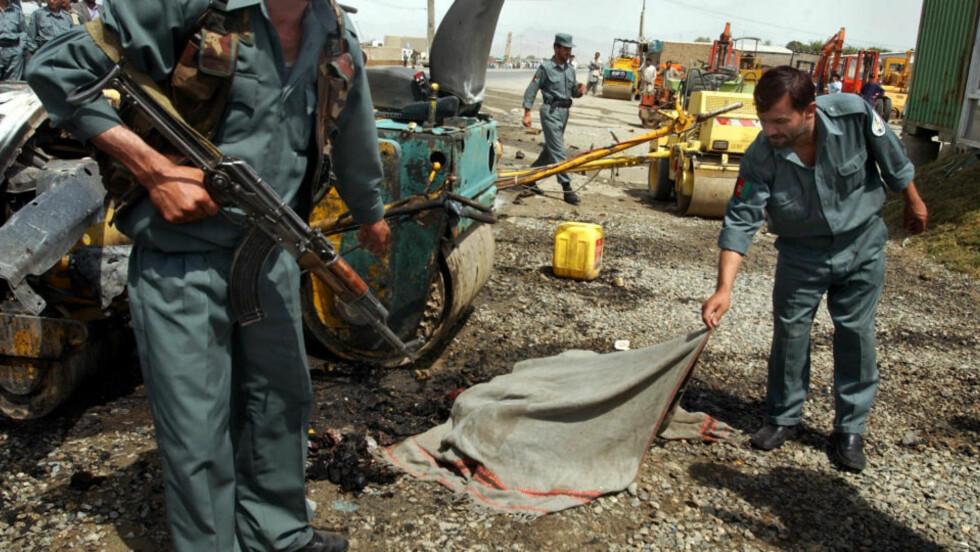 VEIBOMBE: Afghanske soldater dekker til et offer for en veibombe rettet mot britiske soldater i Afghanistan. En tidligere Guantanamo-fange antas nå å stå bak en rekke slike bomber. Foto: Musadeq Sadeq/AP/Scanpix