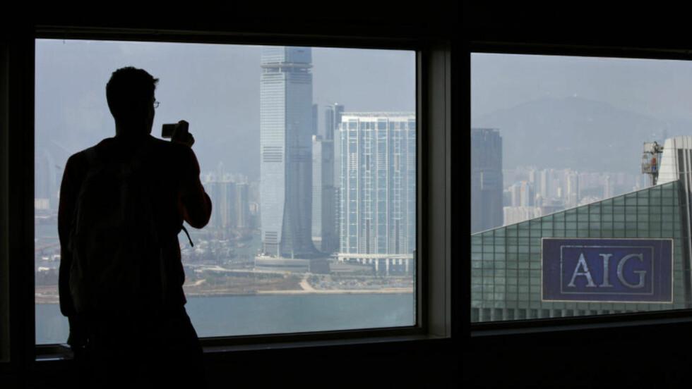 VERDENS STØRSTE VAKLER: En mann tar bilde av AIGs kontorer i Hongkong. Verdens største forsikringsgigant går med store tap hver dag og holder seg flyetnde på skattebetalernes penger. Foto: REUTERS/Bobby Yip/SCANPIX