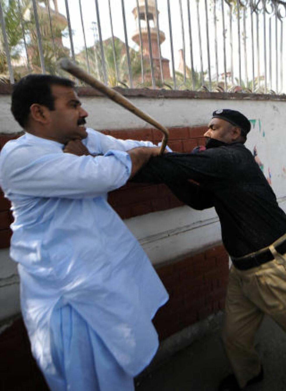 AMPERT: En politimann i håndgemeng med en Sharif-supporter under en demonstrasjon i Lahore i dag. Foto: AFP/SCANPIX