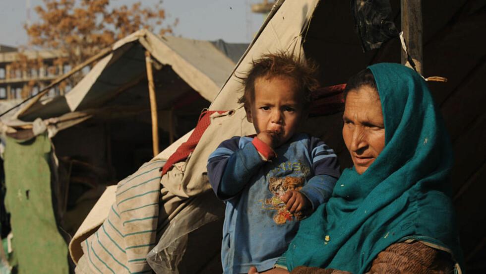 HJELPEARBEID: En afghansk mor og hennes barn sitter i en flyktningeleir i Kabul. Taliban vil straffe vestlige hjelpearbeidere med døden. Foto: Marai Shah/AFP/Scanpix