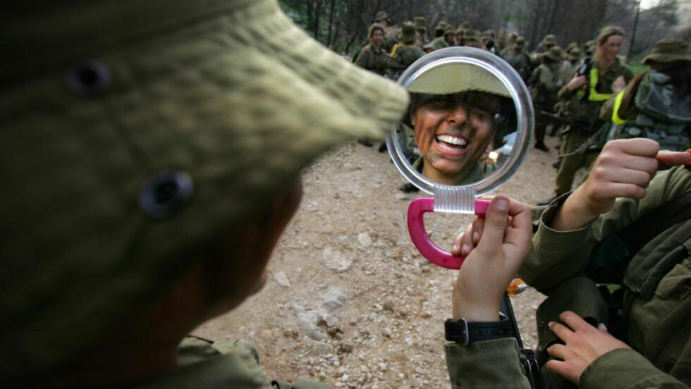 BLID OG FORNØYD: Men hvis denne kvinnelige, israelske soldaten blir tatt i å kysse en medsoldat, blir det bråk. Foto: Oded Balilty/AP/Scanpix