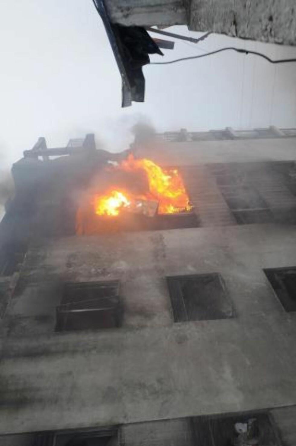 FLAMMER: Flyet krasjet i et høyhus, som tok fyr da flyet styrtet. Foto: Jaime Echeverria/EPA/Scanpix