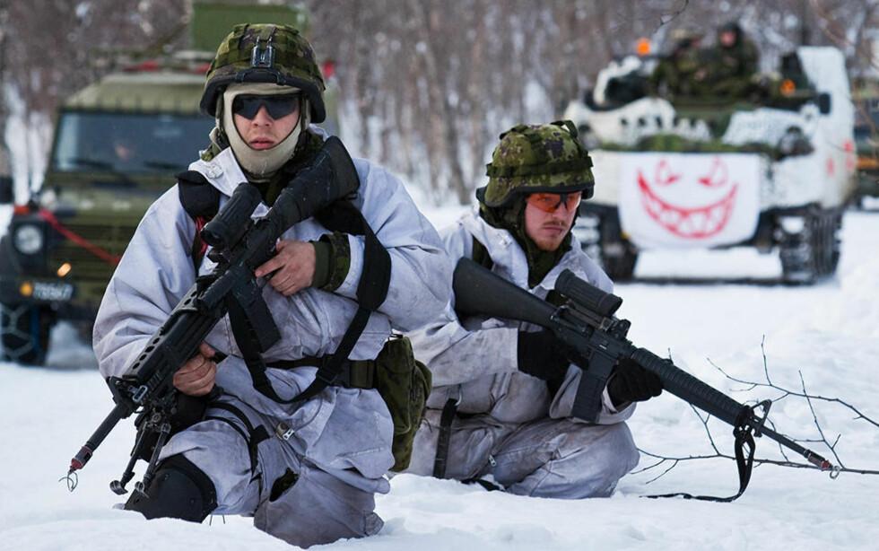 KALDT: To danske soldater forsøker å holde varmen under Cold Response i indre Troms. Begge har på seg norske feltskjorter, vinterkamuflasje og ullundertøy. Foto: Erik Drabløs/Forsvaret