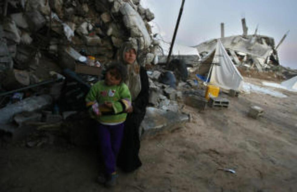ØDELEGGELSER: En palestinsk kvinne og hennes barn utenfor sitt raserte hjem. (AFP PHOTO/MAHMUD HAMS)