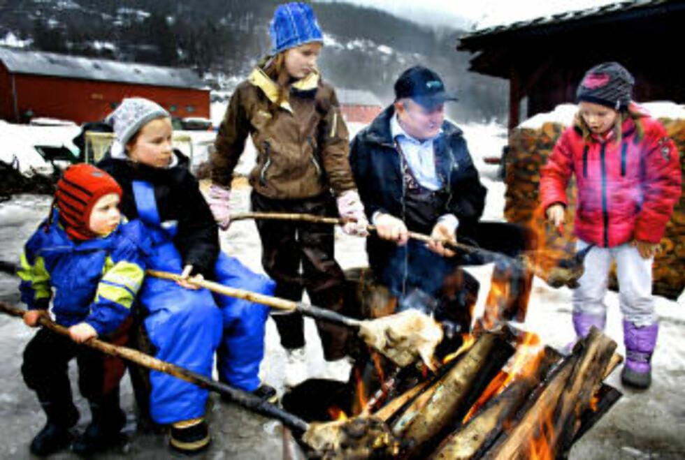 ULLA: Bestefar Ivar L. Løne (69) lærer barnebarna hvordan man svidde smalahovene før de fikk maskinell produksjon. Fra venstre Henrik(3), Hanna(11), Marte (10) og Kari(7).   foto: Ole C. H. Thomassen