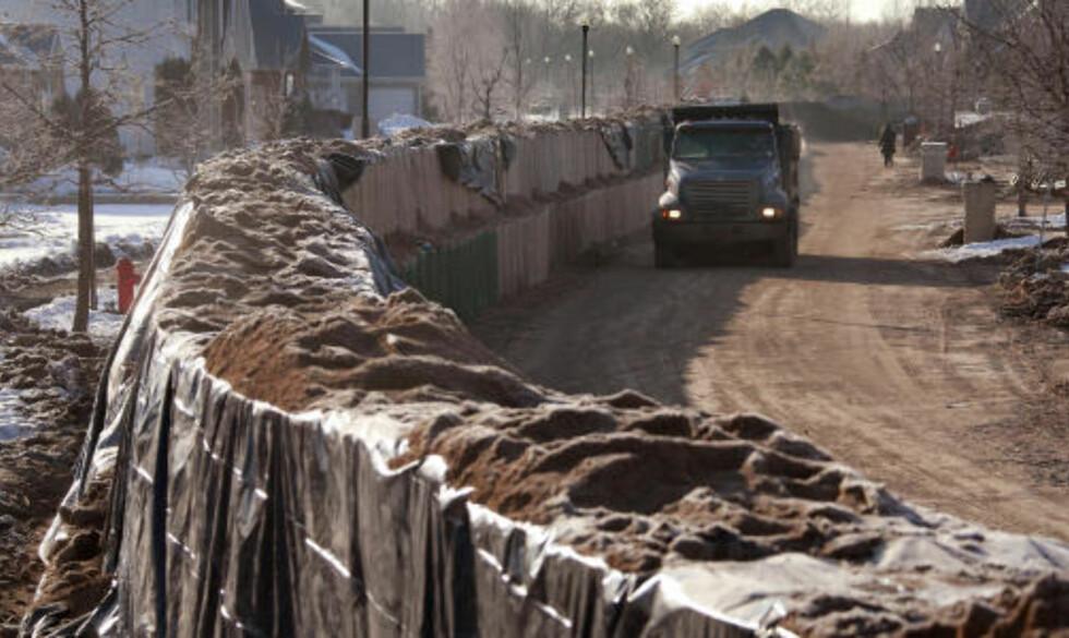HEKTISK ARBEID: Mannskaper fra nasjonalgarden og en stort antall frivillige har lempet sandsekker og bygget ekstre demninger for å sikre byen mot flommen. Foto: AFP/SCANPIX