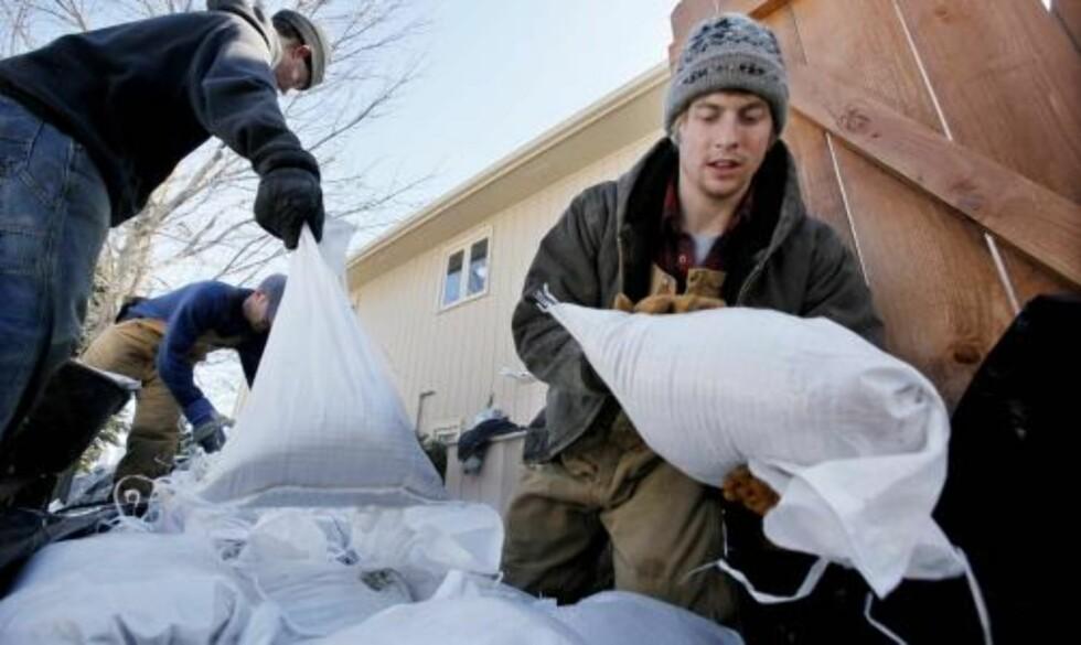 FRIVILLIG: Eric Nies er med som frivillig og bygger sandvegger for å beskytte byen mot vannmassene.  Foto: AP Photo/Elaine Thompson/SCANPIX