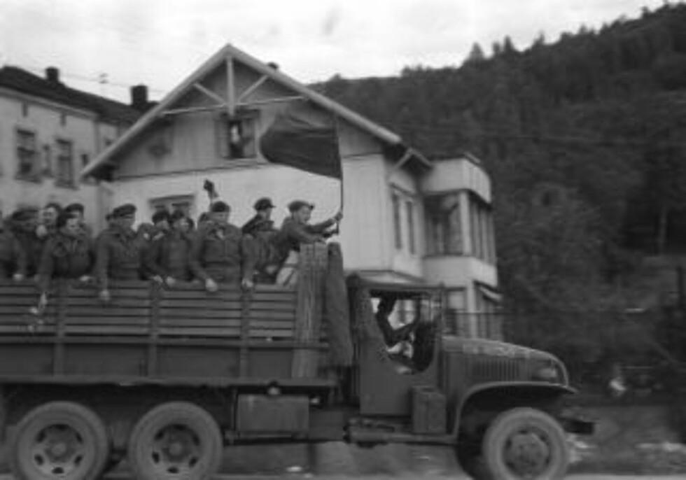 FREDEN: Fredsdagene 1945. Russiske krigsfanger reiser hjem. Her en gruppe glade fanger på vei til samlingsstedet på planet av en lastebil. Ett improvisert rødt flagg vaier i vinden.  Foto: NTB / Scanpix