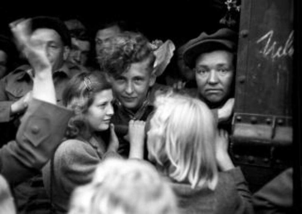 FARVELL: Russiske krigsfanger reiser hjem med tog. Mange nordmenn hadde støttet fangene under deres opphold i Norge, og gode kontakter var knyttet. Avskjeden ble tung for mange. Her en ung kvinne som tar avskjed med en av fangene.  Foto: NTB / Scanpix