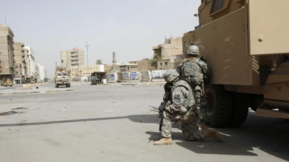 FOLKETOMT: Amerikanske soldater har tatt opp stilling i et veikryss i bydelen Fadhil i Bagdad. Stemningen er svært spent etter at irakiske myndiheter arresterte en sunnimuslimsk militsleder. Foto: AP/Hadi Mizban/SCANPIX