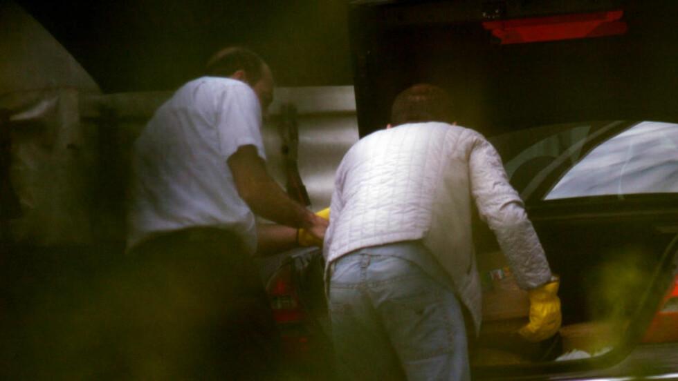 AVSLØRT: Mens de laster 70 kilo hasj inn i bagasjerommet på en personbil, er politiets spanere parat med kameraet.  Foto: KRIPOS