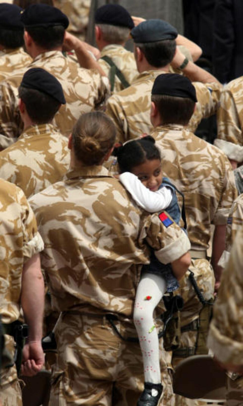 LOKAL PÅ BESØK: Britisk soldat holder et irakisk barn på armen under sermonien. Foto: ESSAM AL-SUDANI/AFP