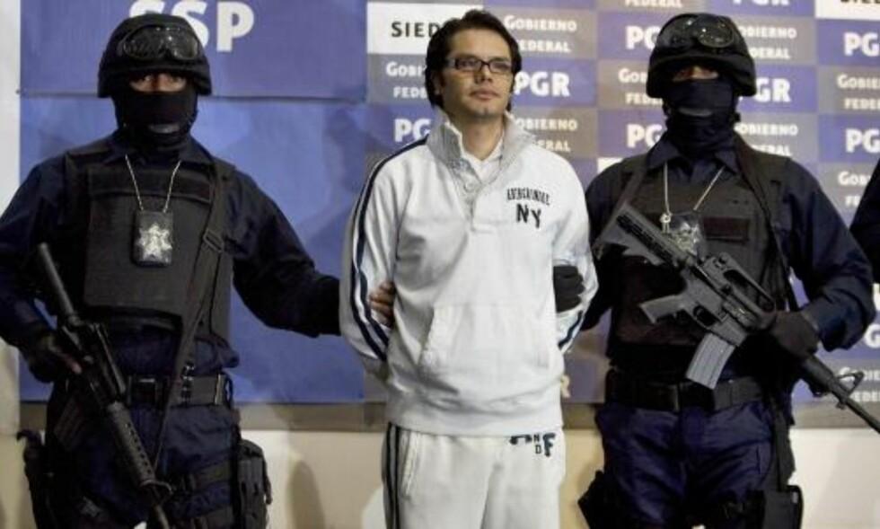PHOTOSHOOT: Med to poserende politimenn ble Leyva presentert for pressen. Foto: SCANPIX/AP Photo/Eduardo Verdugo